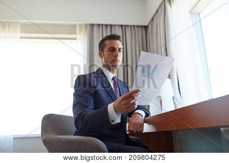 business trip, people and paperwork concept - businessman with papers working at hotel room