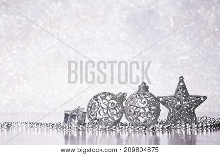 Christmas decoration with gift box, silver balls, garland and star lying lying on a silvery background. New year and Christmas background with copy space for text. Greeting card.