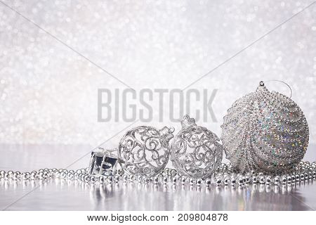 Christmas decoration with silver balls, gift box and garlands lying on a silvery background. New year and Christmas background with copy space for text. Greeting card.