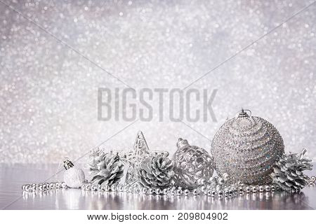Christmas decoration with silver balls, star and garlands lying on a silvery background. New year and Christmas background with copy space for text. Greeting card.