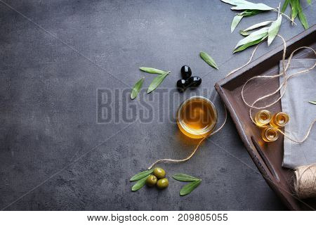 Tray with olives and oil on grunge table