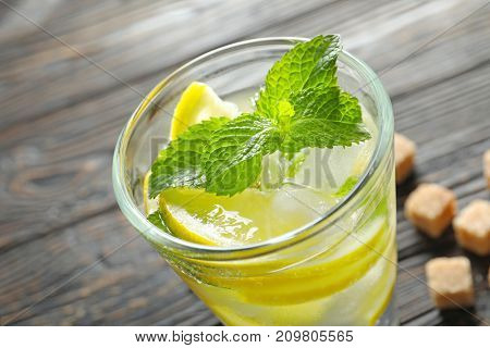 Glass of cocktail with mint and lemon on wooden background