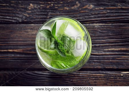 Glass of cocktail with mint and lime on wooden background
