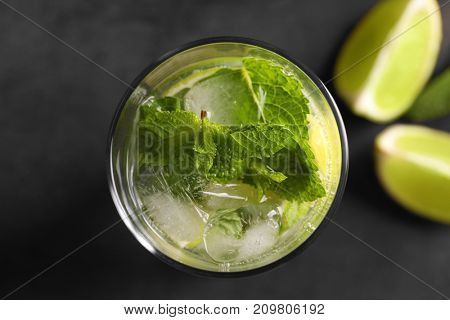 Glass of cocktail with lime and mint on grey background