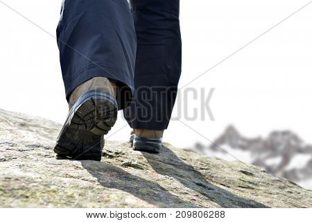 The legs of a mountain hiker with hiking boots on a rock.
