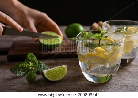 Woman cutting lime for mojito cocktail on wooden table