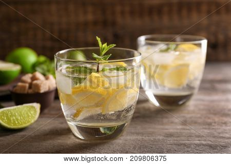 Glasses of cocktail with lemon and mint on wooden table