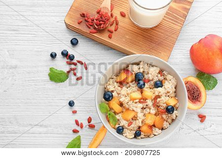 Bowl with oatmeal, peaches and berries on table