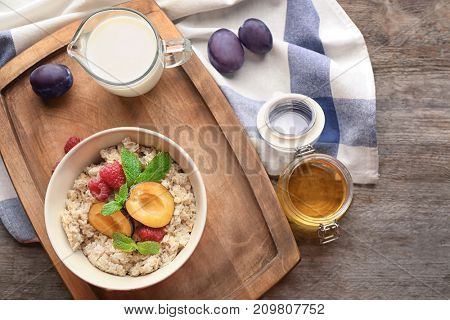 Bowl with oatmeal, fresh plums and raspberries on table