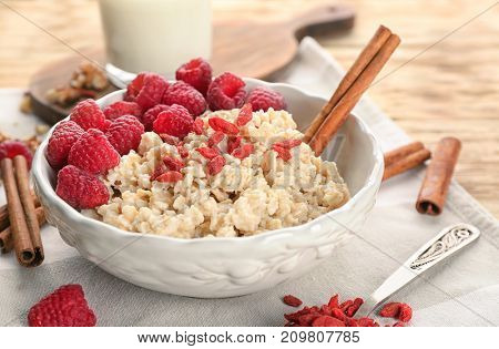 Bowl with oatmeal, raspberries and goji on table
