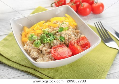 Bowl with oatmeal and vegetables on table