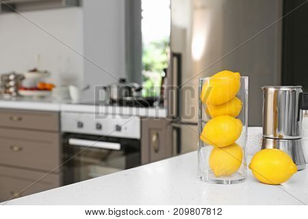 Lemons and coffee maker on table in modern kitchen