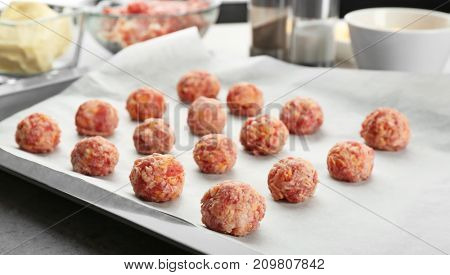 Baking tray with tasty sausage cheese balls on table