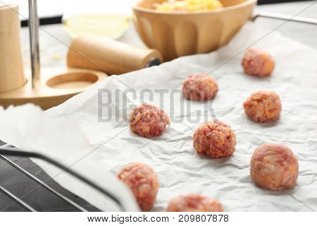 Baking grid with tasty sausage cheese balls on table, closeup