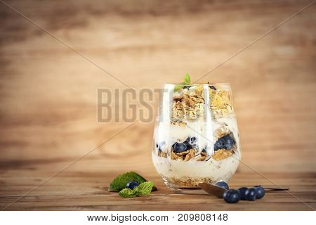 Glass with oat flakes and fresh berries on wooden background