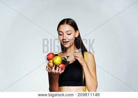 girl in a sporty uniform smiling holding a fresh cucumber fork