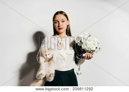 upset girl holding a cat and a bouquet of flowers in her hands
