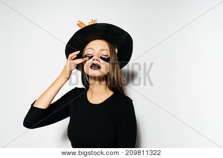 girl puts on a make-up for a costume for halloween