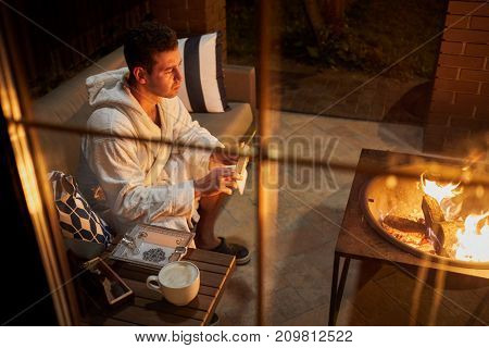 Man in a white bathrobe sits with cigar in his hand and a cup of coffee on the table in front of a portable fireplace.