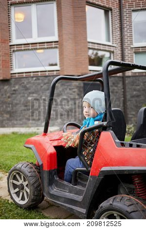 Little boy sits in children car at yard in front of brick cottage.