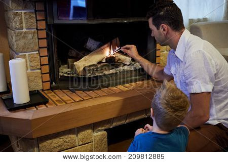 Man and little son sit in front of fireplace in room and light firewoods with big match.