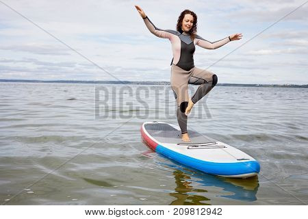 Young woman balances on one leg on inflatable SUP board on water.