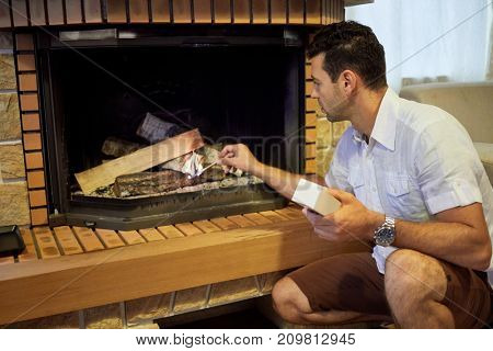 Man sits squatted in front of fireplace in room and lights woods with big match.
