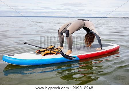 Woman in surfer suit stands in crab position on inflatable SUP board on water.