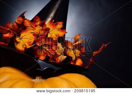 small pumpkin decorated with a hat in a halloween theme
