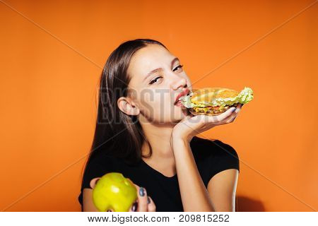 the girl eats a burger instead of an apple in the other hand