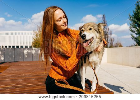 girl walking in the autumn park in the background of the stadium with her dog