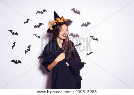girl in costume on halloween laughing surrounded by bats