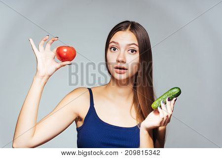 surprised girl holding cucumber and tomato in hands