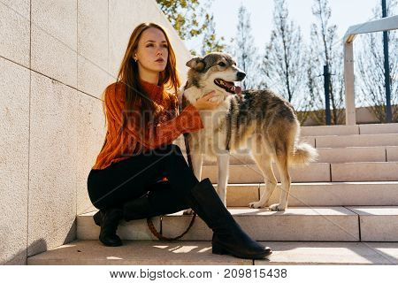 girl in an autumn sweater resting on the steps with her dog