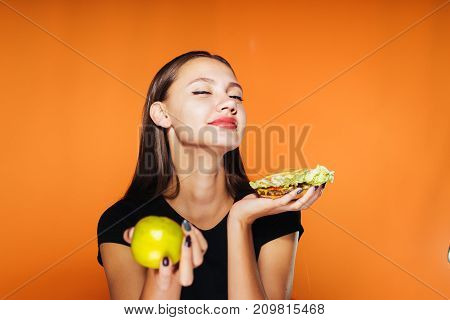 a girl enjoys a burger in her hands holding in another apple