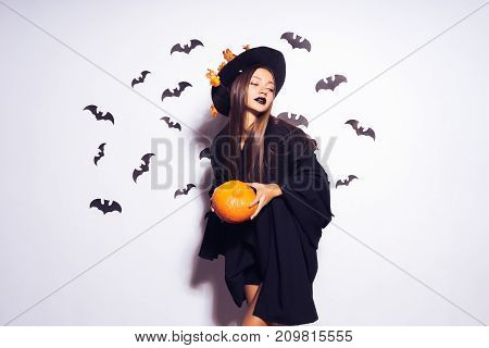 the girl is holding a small pumpkin surrounded by bats