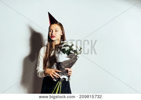 happy girl with a bouquet of flowers in a festive cap