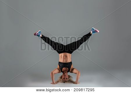 Full length portrait of a muscular adult sportswoman doing handstand exercise isolated over gray background