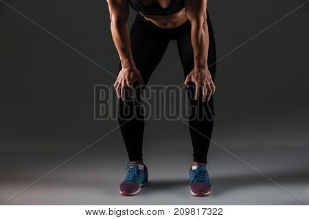 Cropped image of a muscular sportswoman resting with hands on her knees resting isolated over gray background