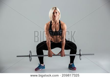 Portrait of a confident muscular adult sportswoman doing squats with a barbell isolated over gray background