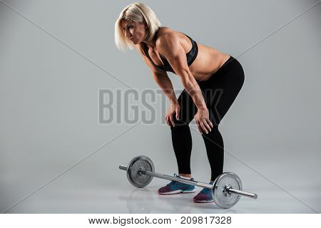 Full length portrait of a exhausted muscular adult sportswoman resting after lifting a heavy barbell isolated over gray background