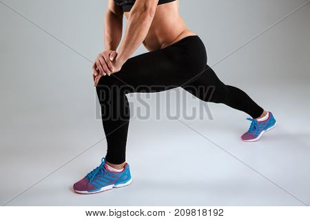 Cropped image of a female athlete in sportswear doing stretching exercises isolated over gray background