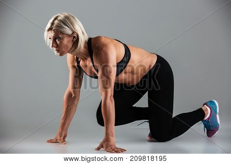 Full length portrait of a concentrated muscular fit sportswoman getting ready to start running isolated over gray background