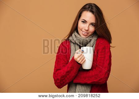 Picture of happy caucasian lady dressed in sweater and wearing scarf standing isolated. Looking camera drinking hot tea.