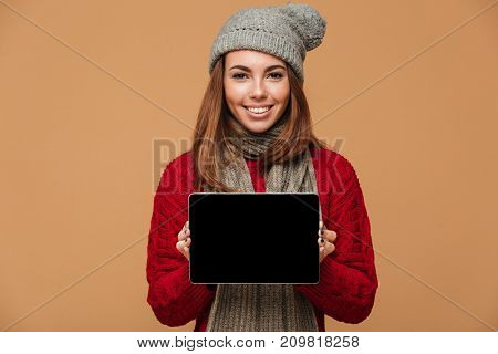 Photo of smiling caucasian lady dressed in sweater and wearing scarf with hat standing isolated. Looking camera showing display of tablet computer.