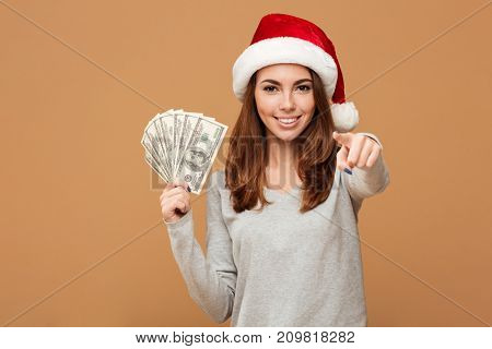 Image of caucasian cheerful lady wearing christmas hat standing isolated holding money. Looking camera pointing to you.