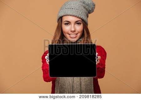 Photo of smiling caucasian lady dressed in sweater and wearing scarf with hat standing isolated. Looking camera showing display of tablet computer. Focus on tablet.