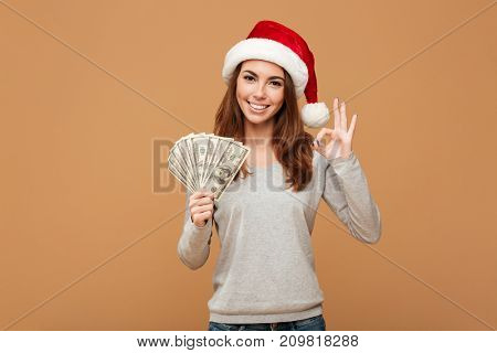 Image of cheerful caucasian lady wearing christmas hat standing isolated holding money showing okay gesture. Looking camera.