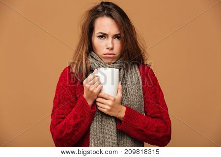 Image of sad sick caucasian woman dressed in sweater and wearing scarf standing isolated. Looking camera drinking hot tea.
