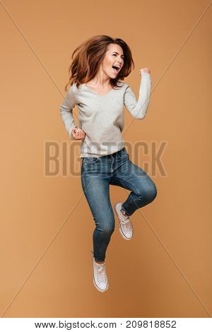Photo of screaming happy caucasian woman jumping isolated make winner gesture.